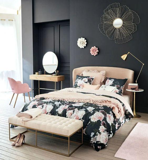 una camera da letto raffinata con pareti nere, un letto marrone chiaro e una panca color crema, una sedia rosa e biancheria da letto floreale