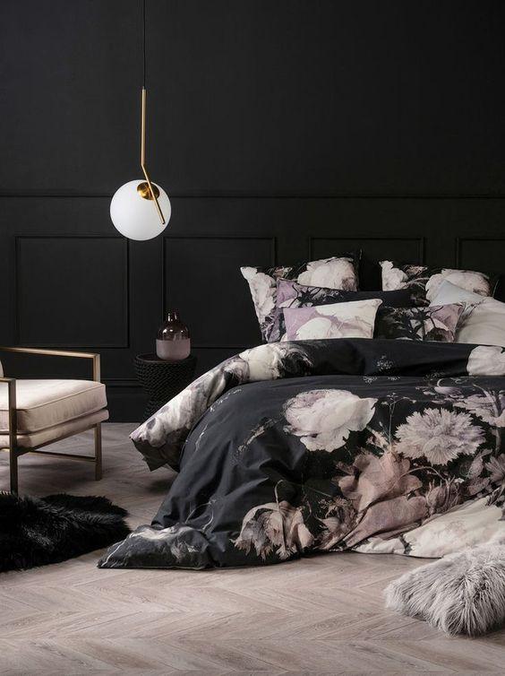 una camera da letto molto raffinata con pareti nere, pannellatura, biancheria da letto floreale nera e rosa, una sedia arrossata e una lampada a sospensione