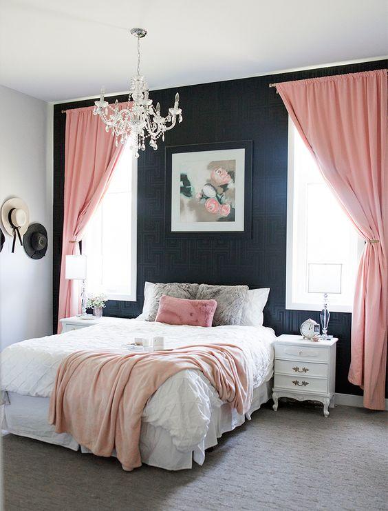 un'elegante camera da letto con carta da parati stampata nera, raffinati mobili bianchi, tessuti rosa e un lampadario di cristallo