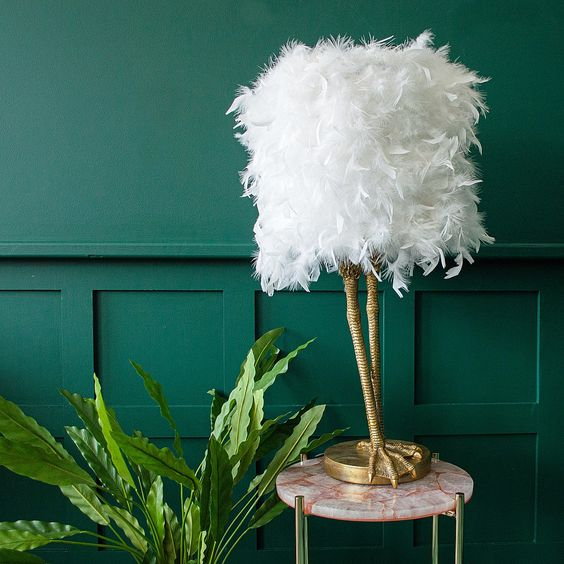 una lampada da tavolo raffinata e stravagante di piume di struzzo bianche e base a forma di gamba d'oro è un'idea molto divertente