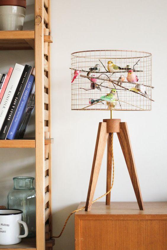 una bizzarra lampada da tavolo a gabbia per uccelli in rame con molti uccelli finti è un'idea divertente e allegra per qualsiasi spazio