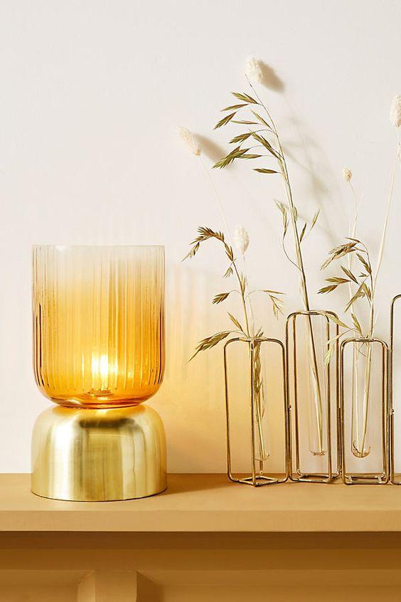 un'elegante ed elegante lampada da tavolo a forma di tazza in vetro colorato e oro è un'opzione chic per uno spazio contemporaneo