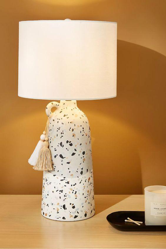 un'elegante lampada da tavolo con vaso in terrazzo veneziano con un elegante paralume bianco e nappe è un'idea accento fresco