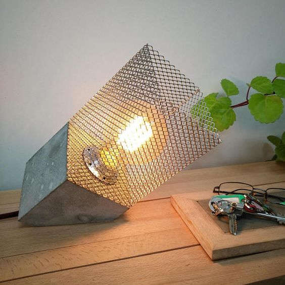una lampada da tavolo industriale in cemento e filo metallico presenta un design molto audace che aggiunge interesse allo spazio