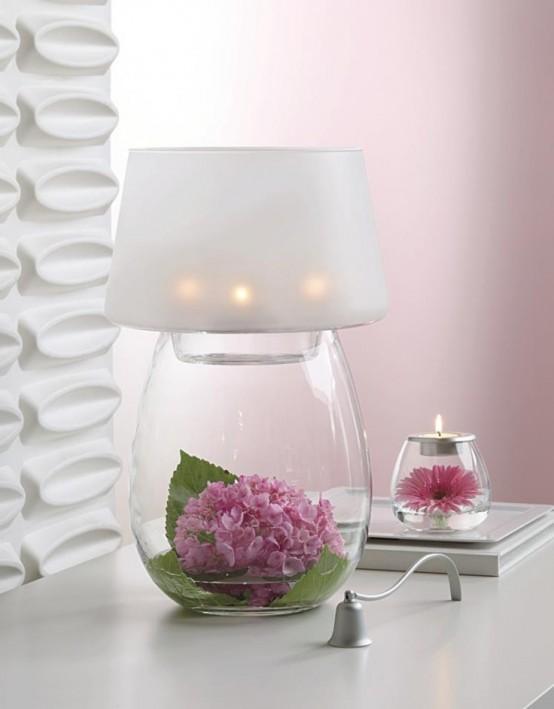 una romantica lampada da tavolo con base in vetro: puoi posizionare qualsiasi cosa all'interno, qui ci sono fiori e vegetazione