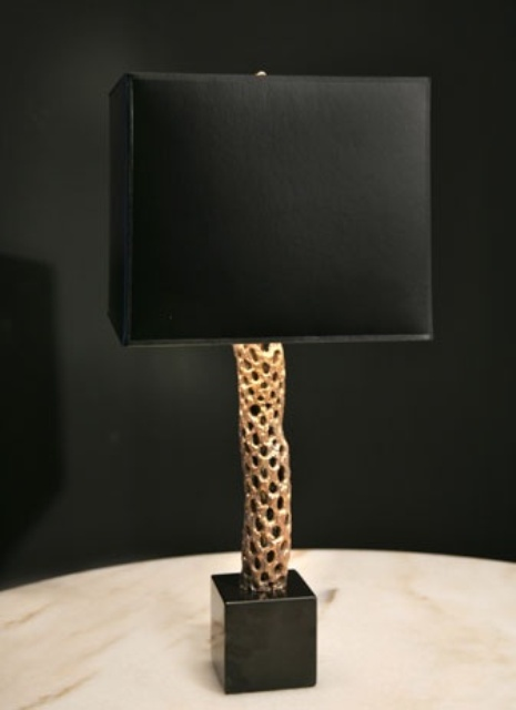 una raffinata lampada da tavolo nera e oro con un elegante paralume e una base materica dorata per aggiungere un tocco sofisticato allo spazio