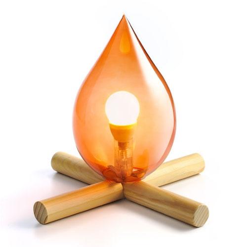 una lampada da tavolo ispirata al fuoco da campo con bastoncini di legno e un paralume in vetro rosso con una lampadina è una soluzione elegante