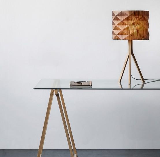un'elegante lampada da tavolo con un paralume geometrico sfaccettato e una semplice base in legno per aggiungere un tocco naturale allo spazio