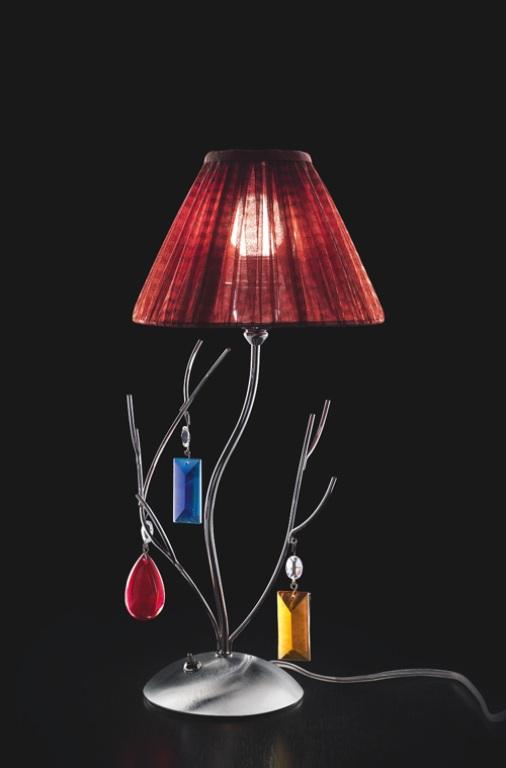 una raffinata lampada da tavolo con rami e gioielli colorati appesi sopra più un paralume bordeaux per uno spazio moderno o contemporaneo