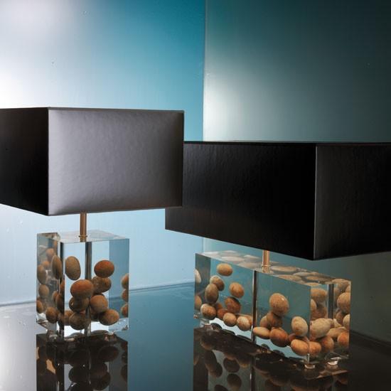 eleganti lampade da tavolo moderne con basi in resina con ciottoli ed eleganti paralumi neri sono audaci e alla moda