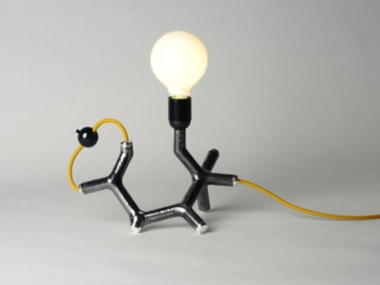 una divertente lampada da tavolo ispirata alla chimica in oro, nero e con una lampadina è un'idea interessante e accattivante