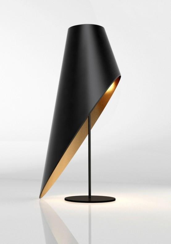 una splendida lampada da tavolo asimmetrica nera e oro con un paralume tagliato è una dichiarazione audace e raffinata per uno spazio moderno