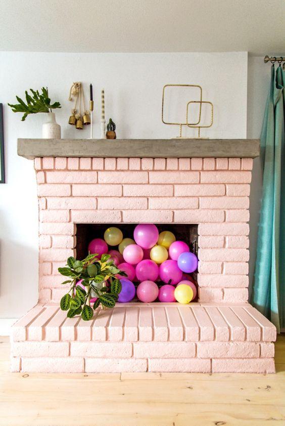 un caminetto in mattoni arrossato pieno di palloncini colorati e con piante in vaso tutt'intorno è un'idea molto allegra e divertente