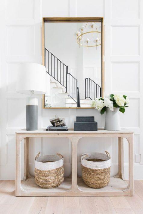 un ingresso moderno chic con un grande specchio, una graziosa consolle in legno con cesti e una lampada a blocchi di colore è semplice ed elegante