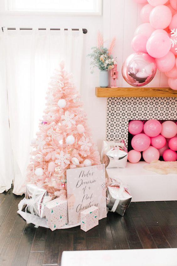 un albero di Natale arrossato con ornamenti bianchi, scatole regalo stampate, palloncini rosa nel camino e sopra