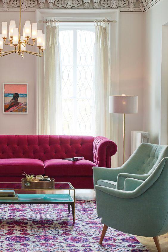 un bel soggiorno con un divano rosa caldo, sedie verde pastello, un lampadario chic, un audace tappeto boho, un tavolo basso e tende neutre