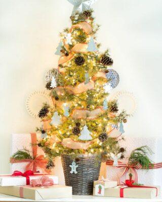 un albero di Natale bello e chic in un cestino, con pigne, mini ornamenti a forma di albero, fiocchi di neve e luci più un cappello a cilindro a stella