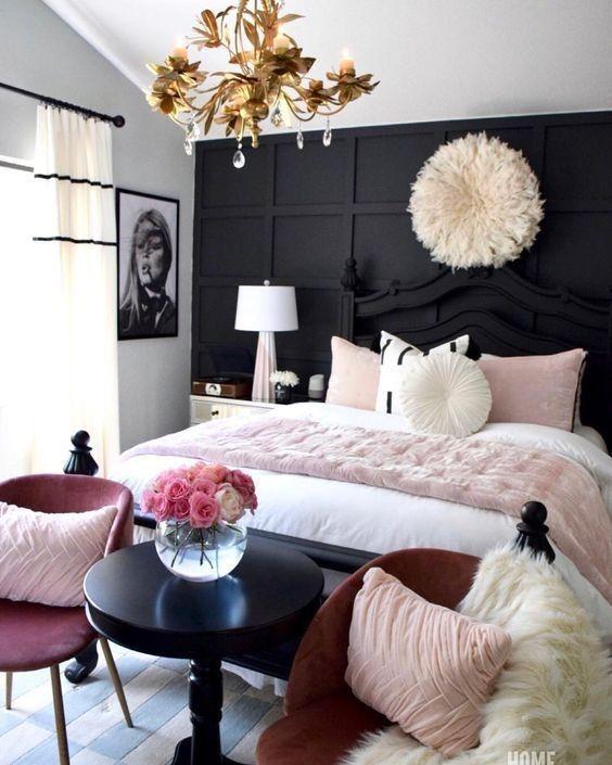 una camera da letto nera, bianca e rosa chiaro con un lampadario in oro e cristallo, un pezzo soffice, cuscini arrossati e un'opera d'arte