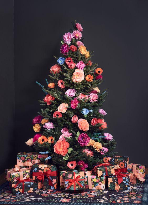 un bellissimo e colorato albero di Natale decorato con finte fioriture in tutte le sfumature possibili è un'idea cool fuori dagli schemi