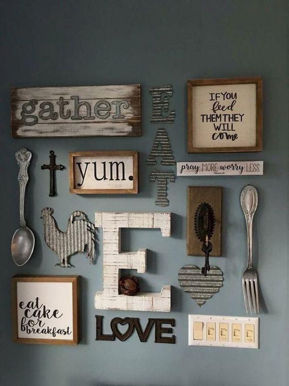 una parete della galleria della cucina di una fattoria con segni incorniciati e senza cornice, con lettere, monogrammi e sagome di legno e metallo