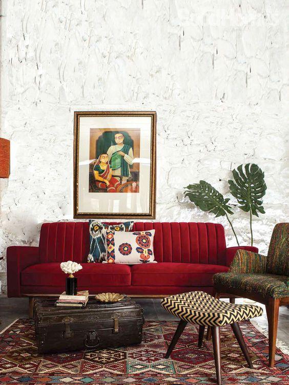 un bellissimo soggiorno con pareti accattivanti, un divano rosso scuro, mobili stampati e un tappeto e una valigia vintage per riporre gli oggetti