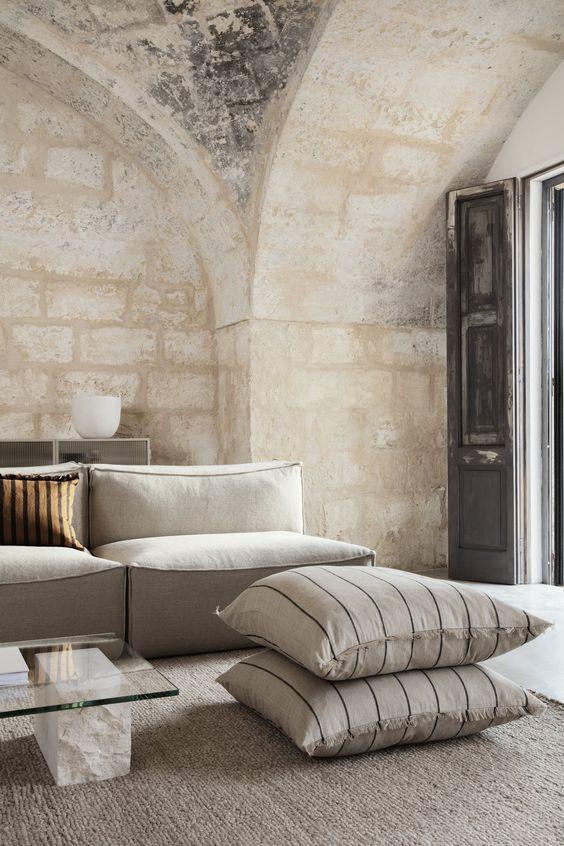 un bellissimo soggiorno neutro con un divano basso color crema, cuscini, un tavolino da caffè in marmo e vetro e pareti in pietra