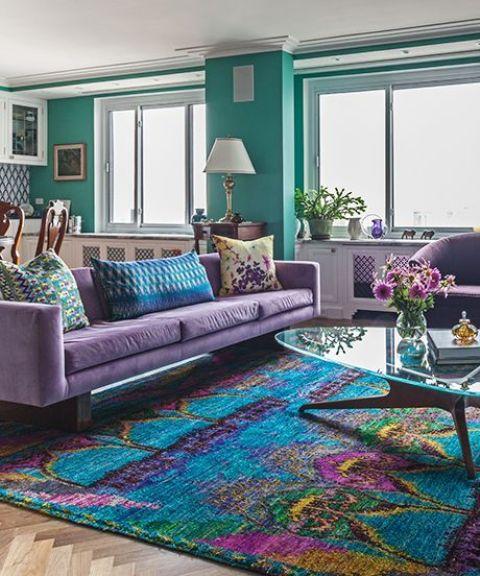 un luminoso soggiorno con pareti verdi, un divano viola e sedie, un tappeto luminoso con tocchi viola e un tavolino in vetro