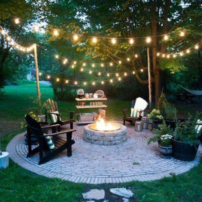 un pozzo del fuoco nel cortile con luci stringa sullo spazio è caldo e accogliente e sembra molto bello