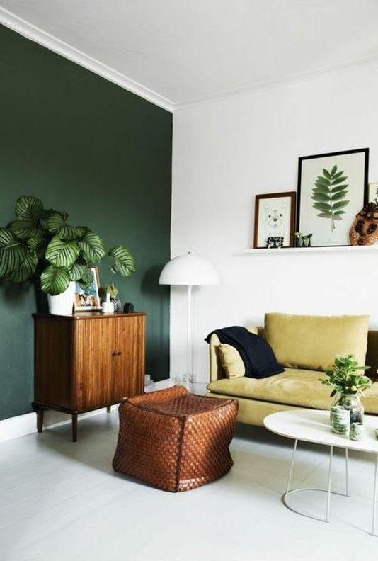 un soggiorno boho con una parete verde scuro, un divano giallo, piante in vaso e una parete della galleria su una sporgenza
