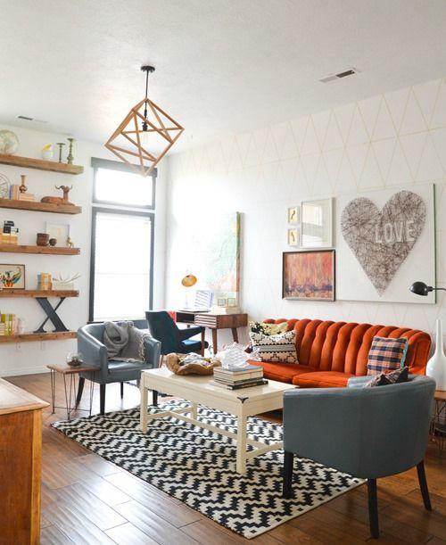 un bellissimo soggiorno moderno della metà del secolo con mensole sospese, un divano arancione, sedie grigie, un tavolo basso e una lampada a sospensione geometrica