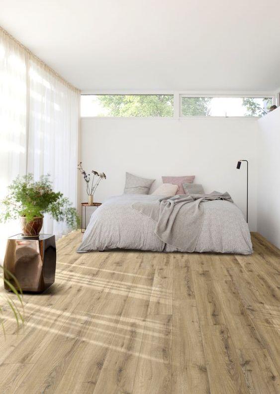 una camera da letto minimalista chic con pareti bianche, una parete vetrata e finestre a lucernario, un letto con lenzuola grigie e alcune piante