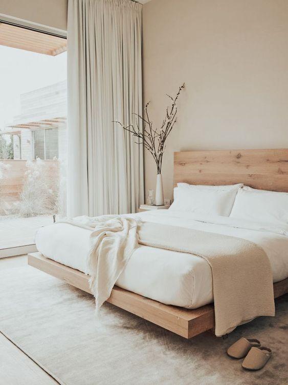 una camera da letto neutra e ariosa è piccola ma sembra più grande grazie a una combinazione di colori neutri e una parete di vetro che porta molta luce
