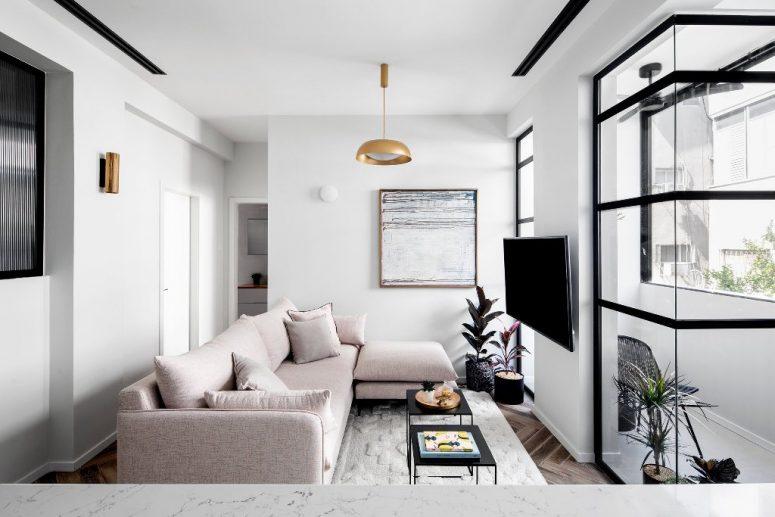 Il soggiorno presenta un componibile arrossato, un'opera d'arte, tocchi in ottone e un ingresso al balcone