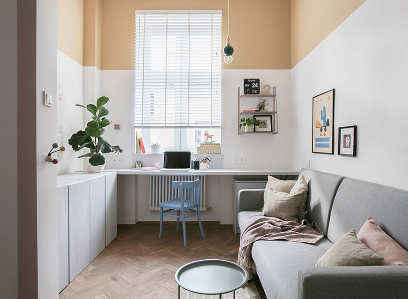 Il soggiorno dispone di un divano, un tavolo e un comodo spazio di lavoro sul davanzale della finestra, le pareti color block rendono la stanza accattivante e allegra