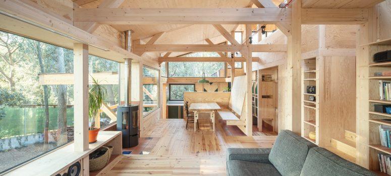 La sala da pranzo dispone di diverse finestre, un focolare e un tavolo da pranzo con sedie e una panca