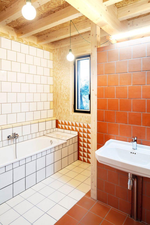 Il bagno è fatto con piastrelle bianche e terracotta e ancora un po 'di legno