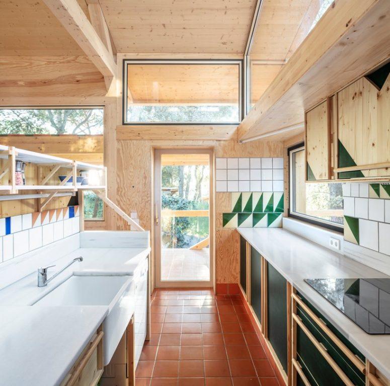 La cucina è realizzata con armadi in legno neri, bianchi e neutri, piastrelle bianche e verdi