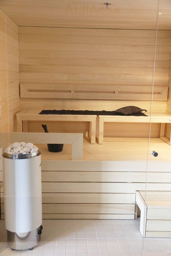 un'elegante sauna in legno imbiancato con diverse panchine e solo un po 'di luce è accogliente