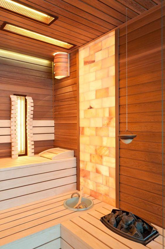 un fresco bagno turco rivestito in legno e con una parte in piastrelle di mosaico, con alcune luci incorporate, è audace e accogliente
