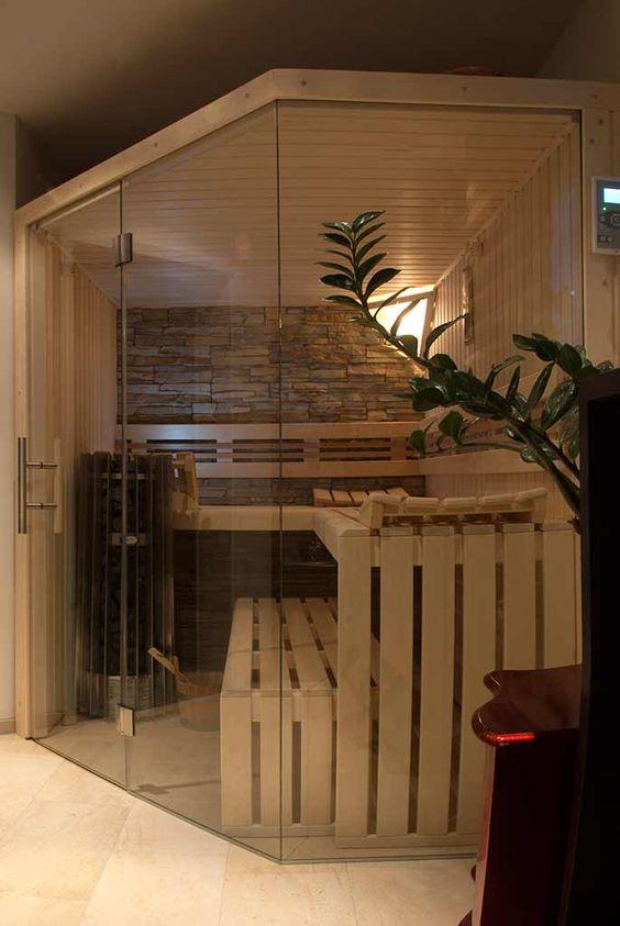 un'accogliente sauna domestica con panche in legno, un muro in pietra e un po 'di luce intima più una parete di vetro