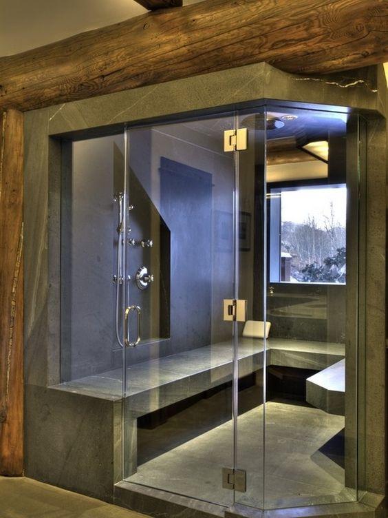 un moderno bagno turco rivestito di pietra grigia, con una finestra e una lunga panca sembra molto spigoloso e audace
