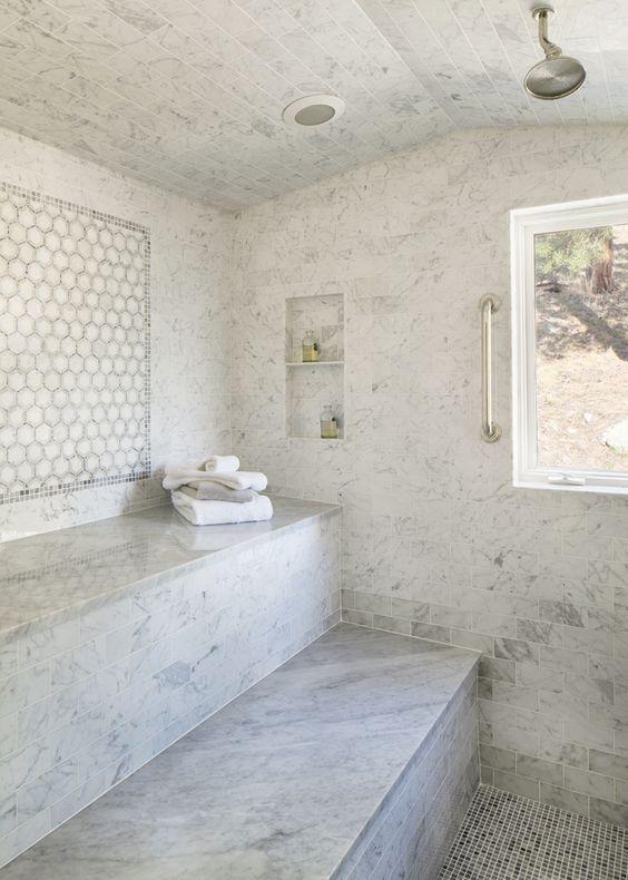 un lussuoso bagno turco in piastrelle di marmo bianco con due lunghe panchine, nicchie e una finestra per godersi il panorama