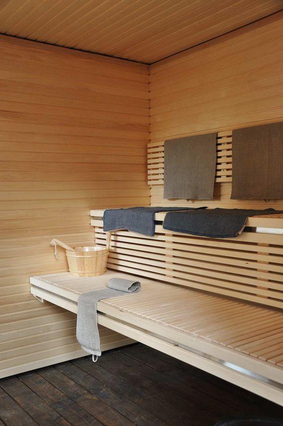 una grande e accogliente sauna rivestita in legno con due panche galleggianti e alcuni asciugamani si sta riscaldando