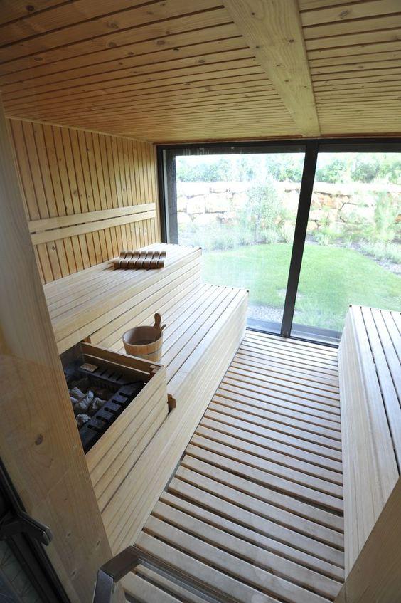 una sauna domestica con una parete di vetro, rivestita di legno è molto accogliente e molto invitante