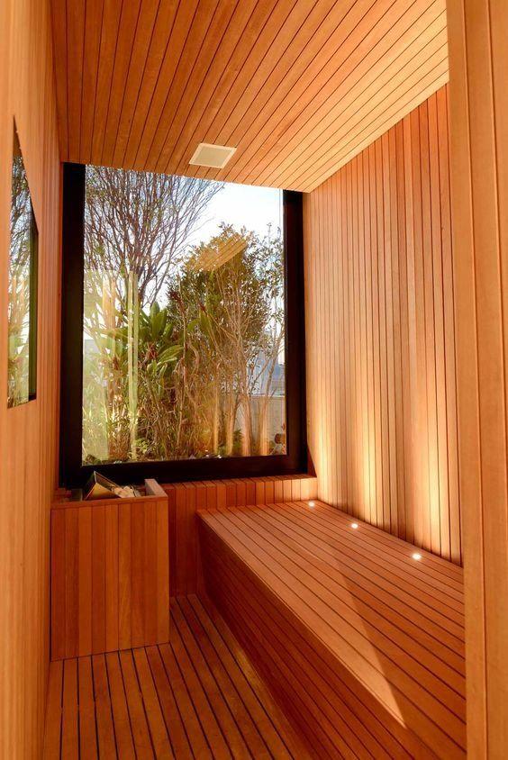 un bagno turco minimalista con una parete di vetro e una panca lunga e ampia più luci incorporate