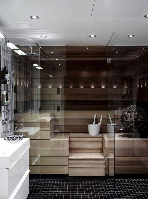 una piccola e chic sauna rivestita in legno con panche e luci integrate e con pareti in vetro fumé
