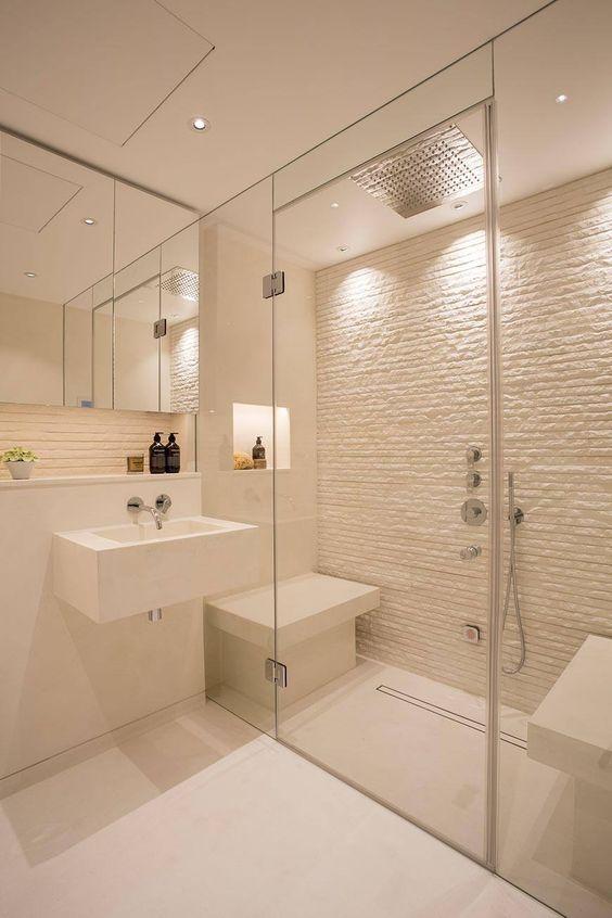 un bagno di vapore bianco piccolo ma chic con un muro di pietra e mini panchine più luci incorporate è bello