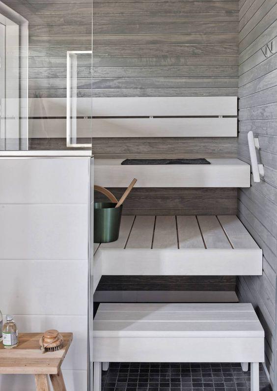 un piccolo bagno turco minimalista rivestito con legno stagionato e con panche imbiancate a calce