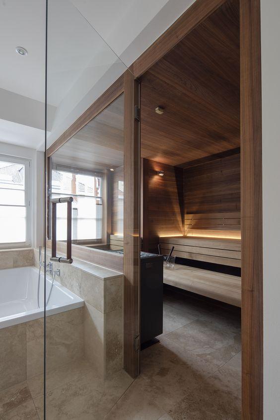 una sauna moderna ed elegante con una parete di vetro, legno dappertutto e un po 'di luce intima per un ambiente
