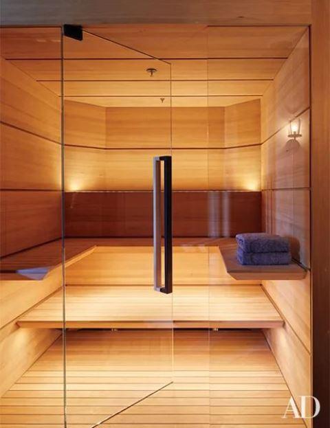 un piccolo ma accogliente bagno turco rivestito in legno con un paio di panchine lungo il muro e luci incorporate